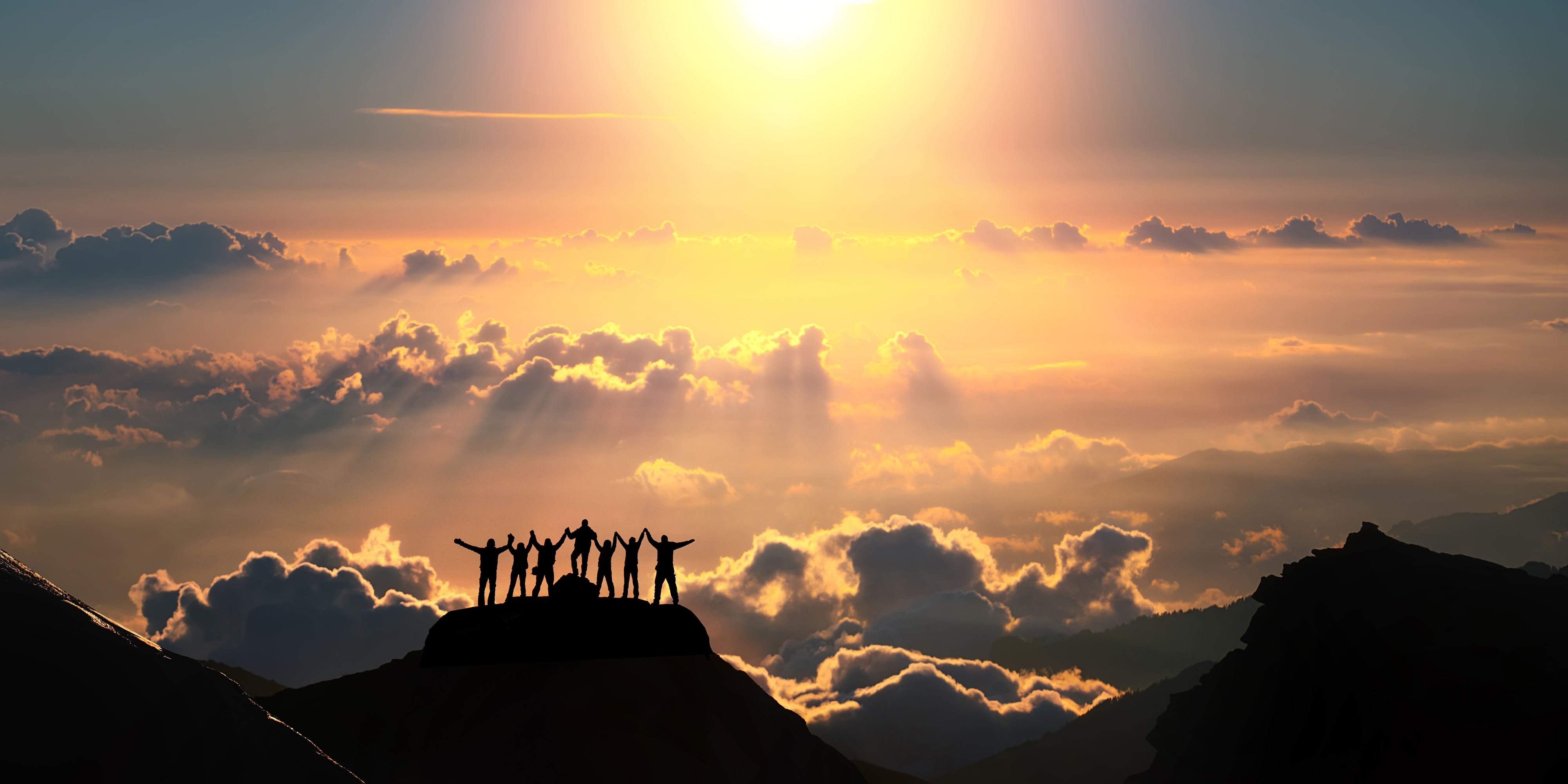 Team of people standing together on top of a mountain